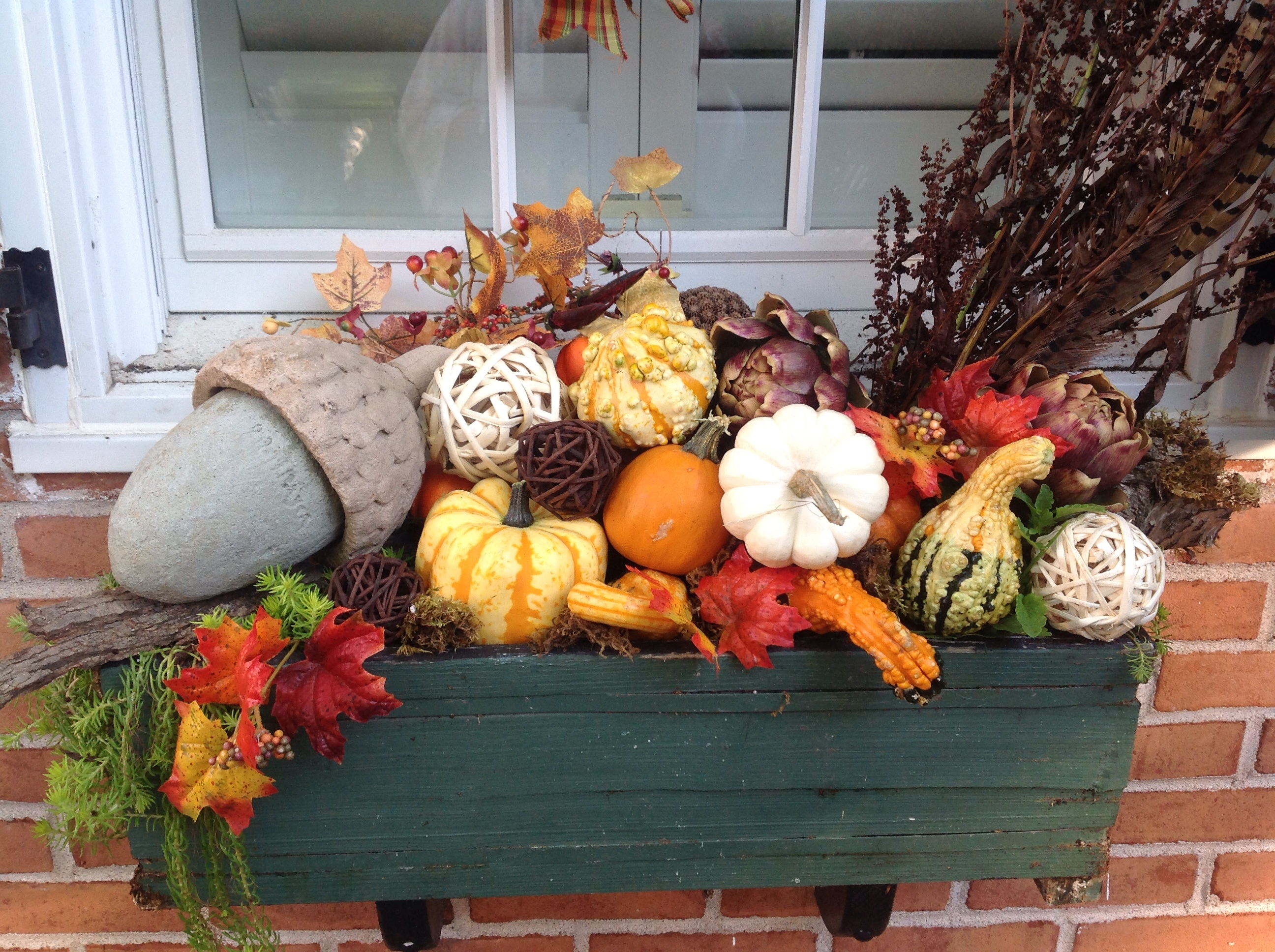 Window box full of fall pumpkins, squash and gourds.